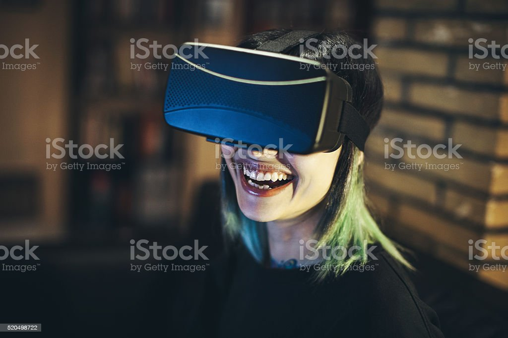 Young woman looks fascinated into Virtual Reality Headset stock photo