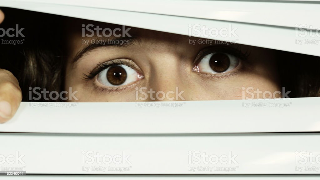 Young woman looks through blinds, brown eyes wide and fearful stock photo