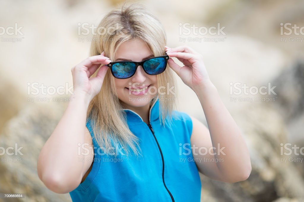 Young woman looks through tinted sunglasses at camera stock photo