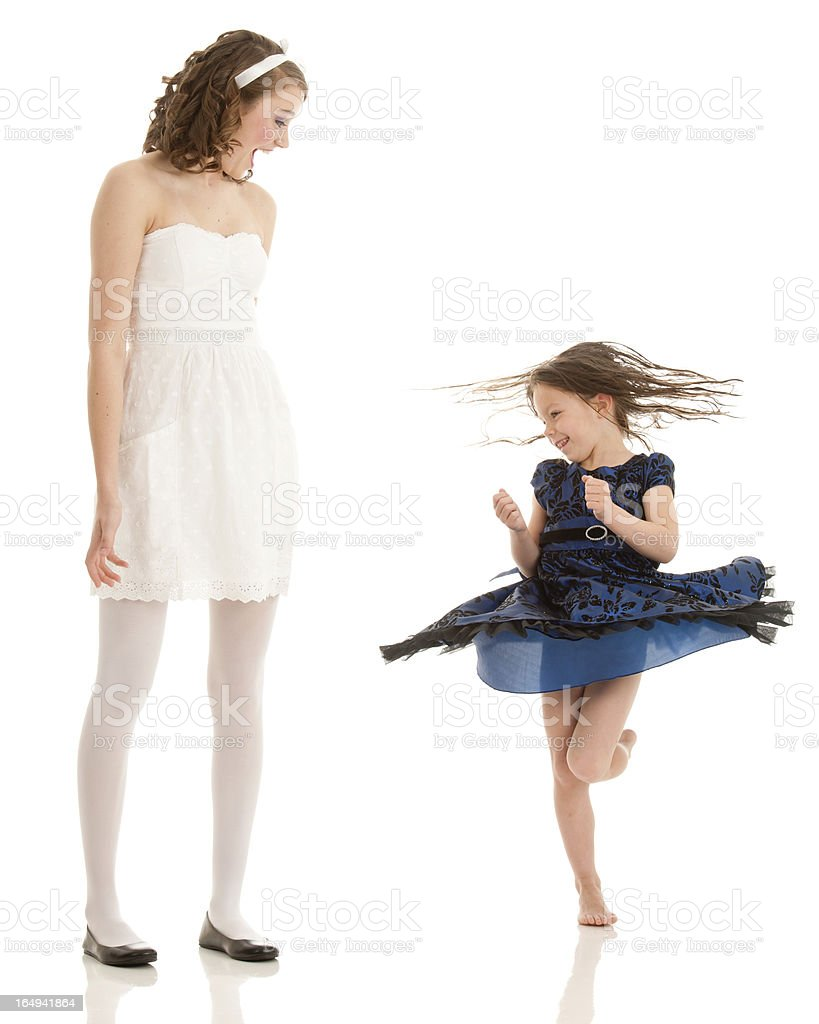 Young woman looks with excitement at spinning dancing girl stock photo