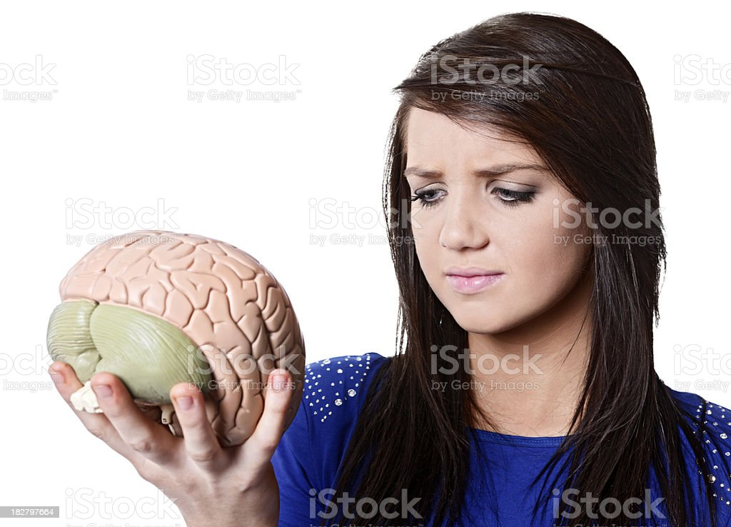 Young woman looks worriedly at model of human brain royalty-free stock photo