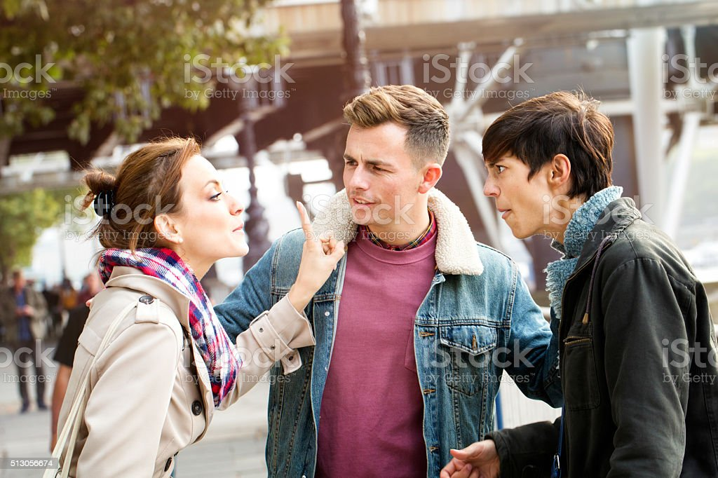 Young woman loses it and acts rudely towards friends stock photo