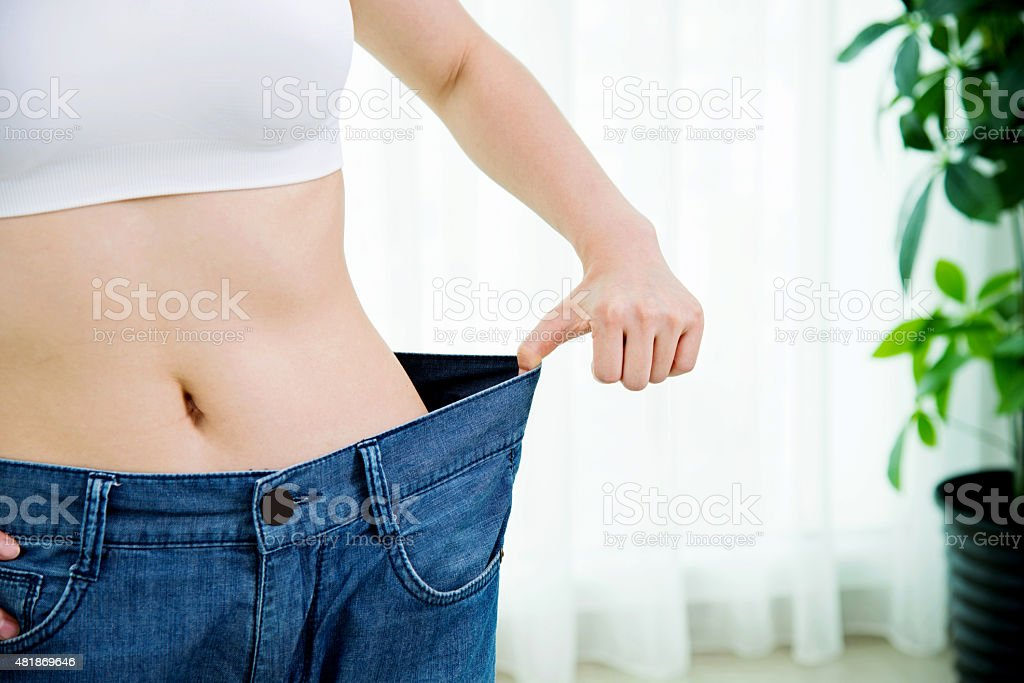 Young woman losing weight stock photo