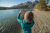 Young woman loving nature making heart shape
