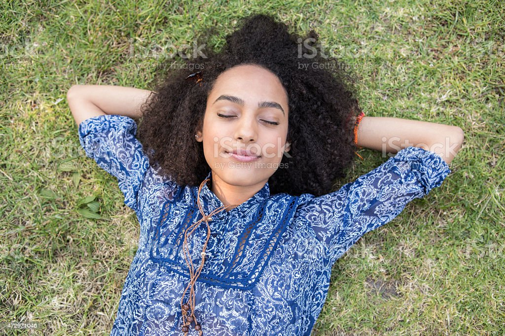 Young woman lying down and napping at a park stock photo