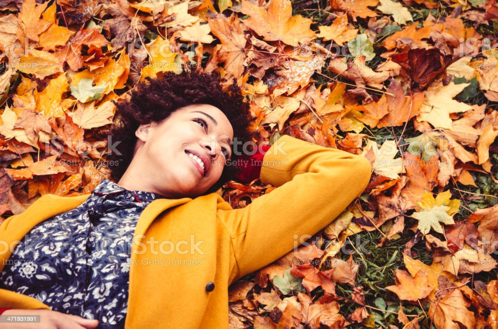 Young woman lying down on autumn leaves stock photo