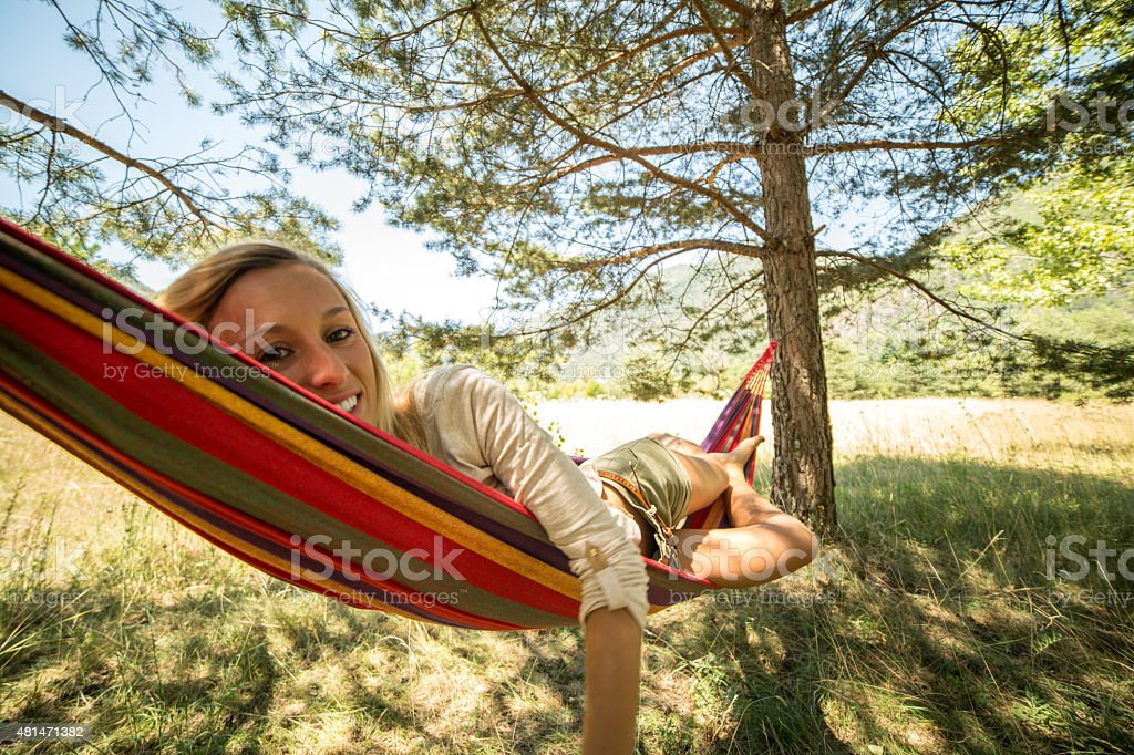 Young woman lying down on hammock enjoying nature in summer stock photo