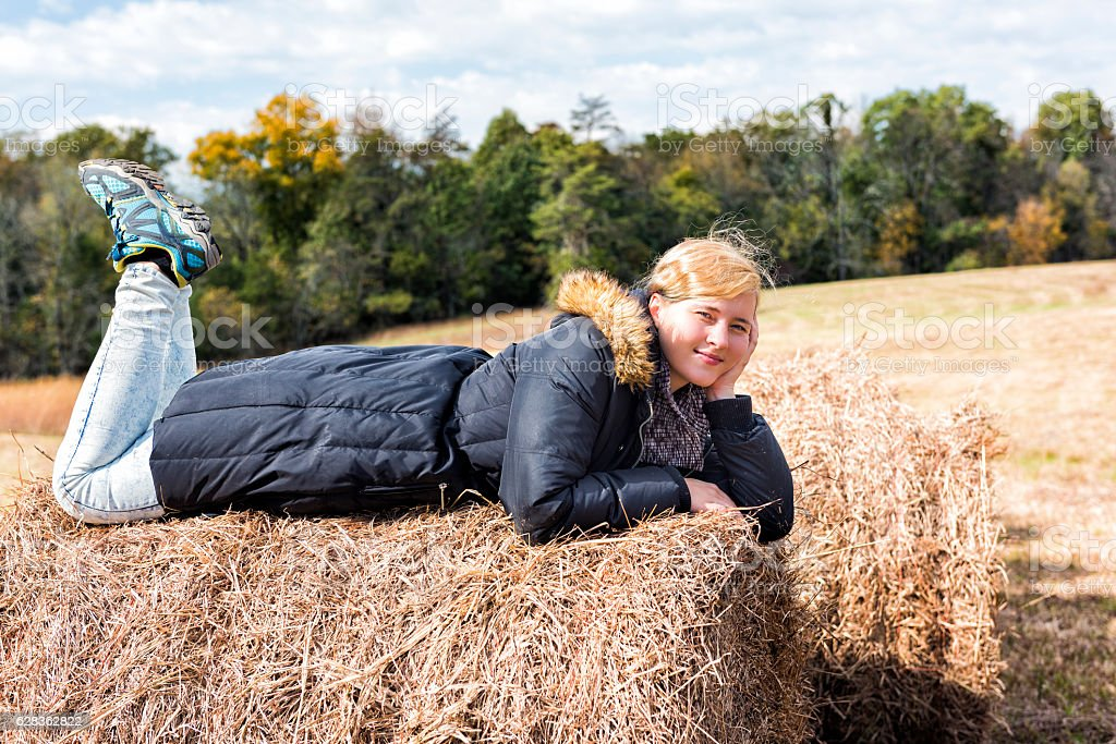 Young woman lying down on hay roll bale stock photo