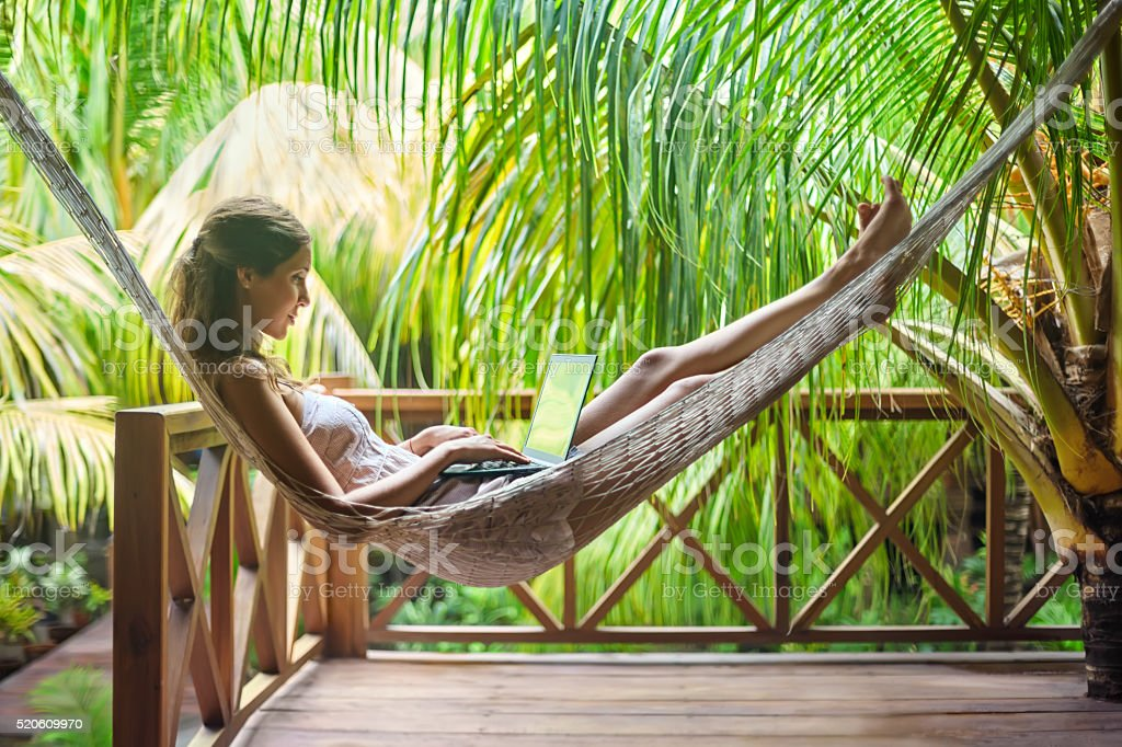 Young woman lying in a hammock with laptop stock photo