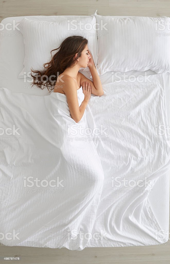 Young woman lying in bed stock photo