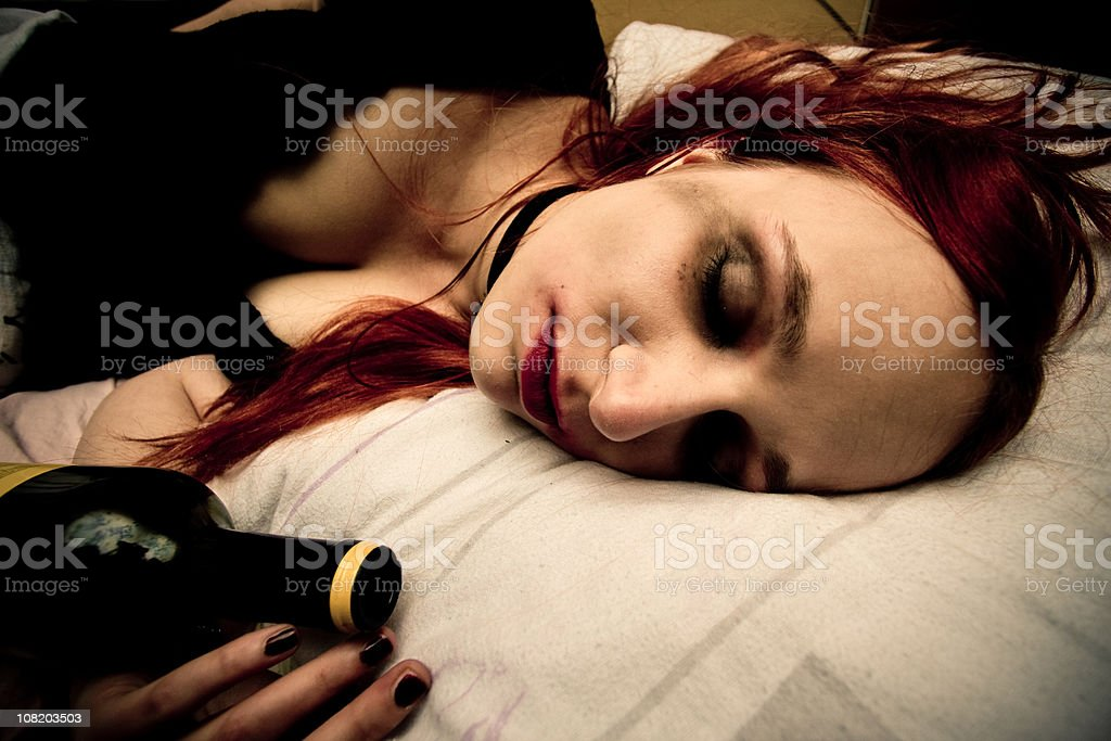Young Woman Lying in Bed with Bottle of Wine royalty-free stock photo