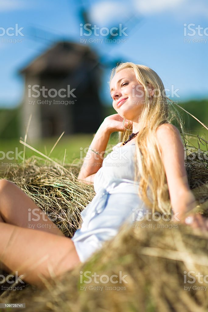 Young Woman Lying in Grass near Windmill royalty-free stock photo