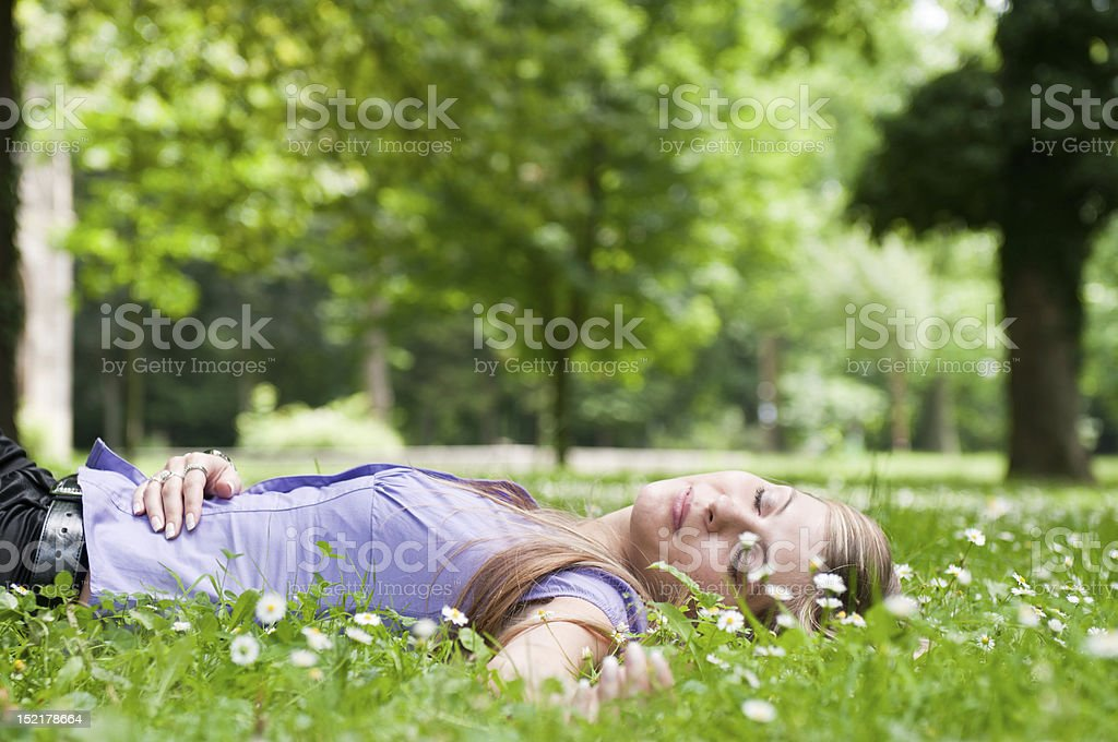 Young woman lying in grass with flowers royalty-free stock photo
