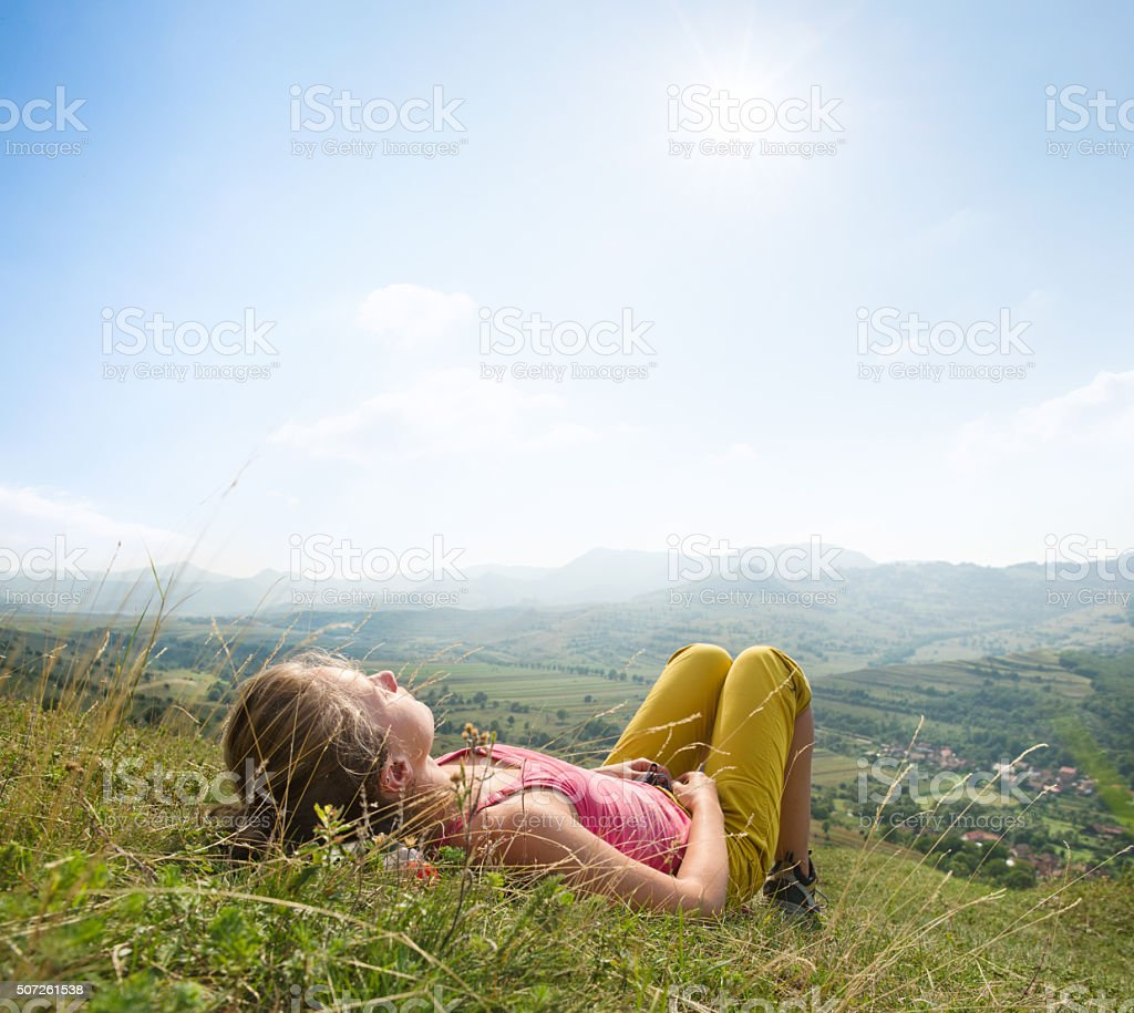 Young woman lying in the grass stock photo