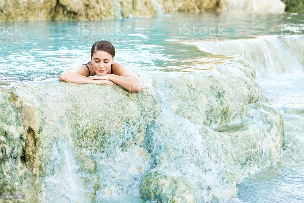 Young woman lying in the natural pool, Saturnia, Italy stock photo