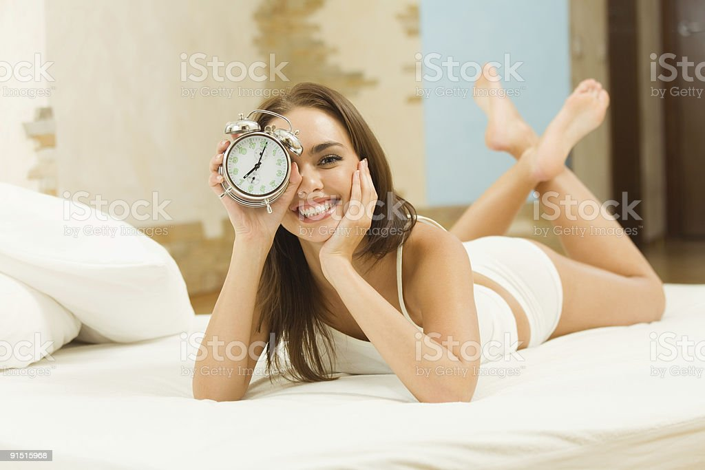 A young woman lying on a bed and holding up an alarm clock royalty-free stock photo