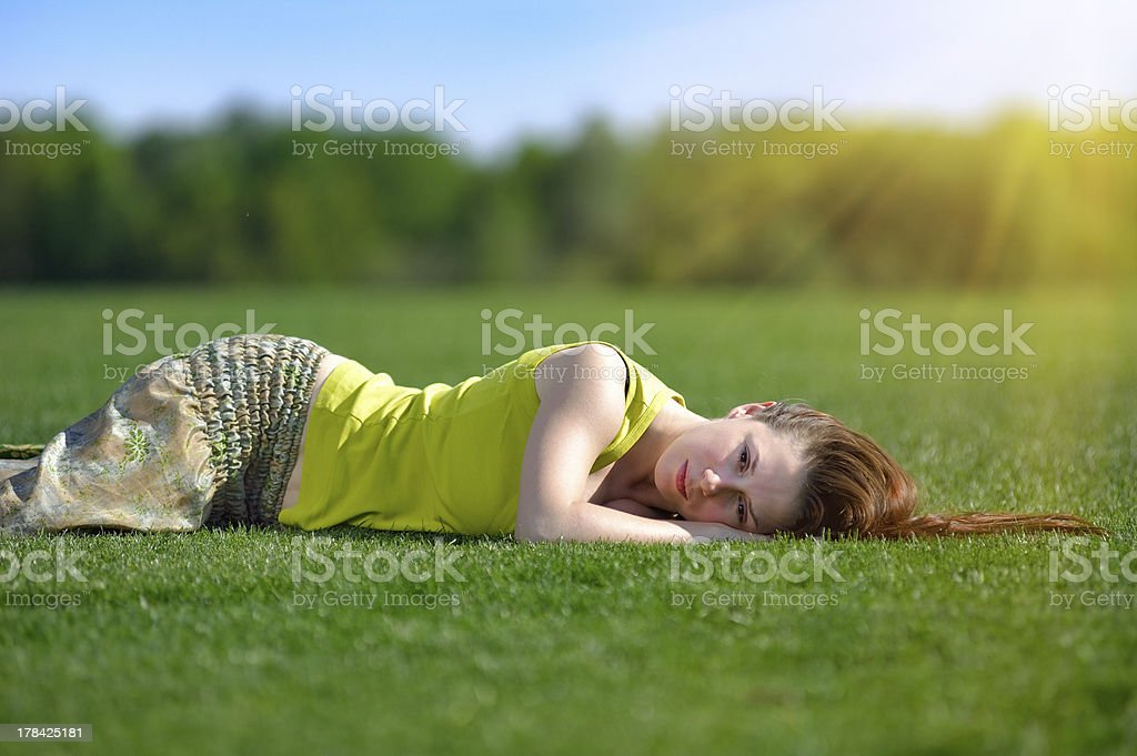Young woman lying on a green meadow royalty-free stock photo