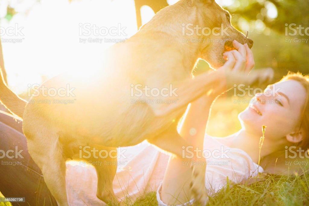 young redhead woman play with her small Mixed-breed dog