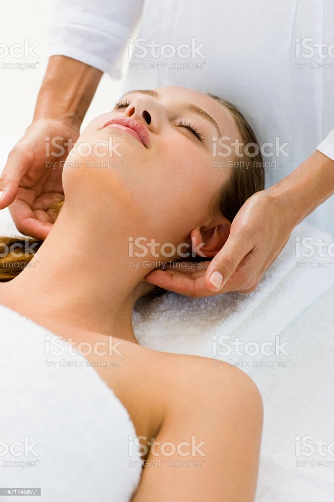 Young woman lying on back receiving head massage royalty-free stock photo