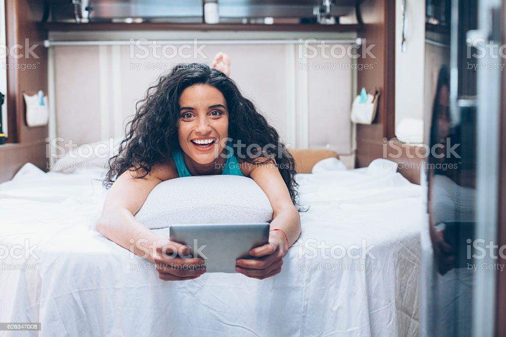Young woman lying on bed and using digital tablet stock photo