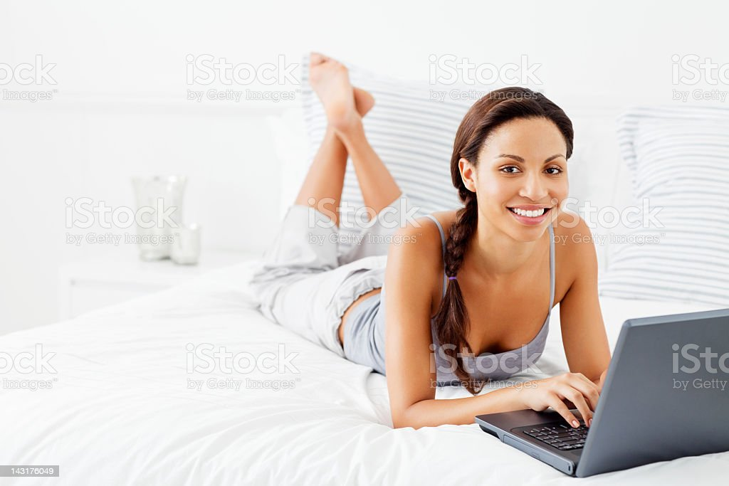 Young Woman Lying on Bed Using Laptop royalty-free stock photo