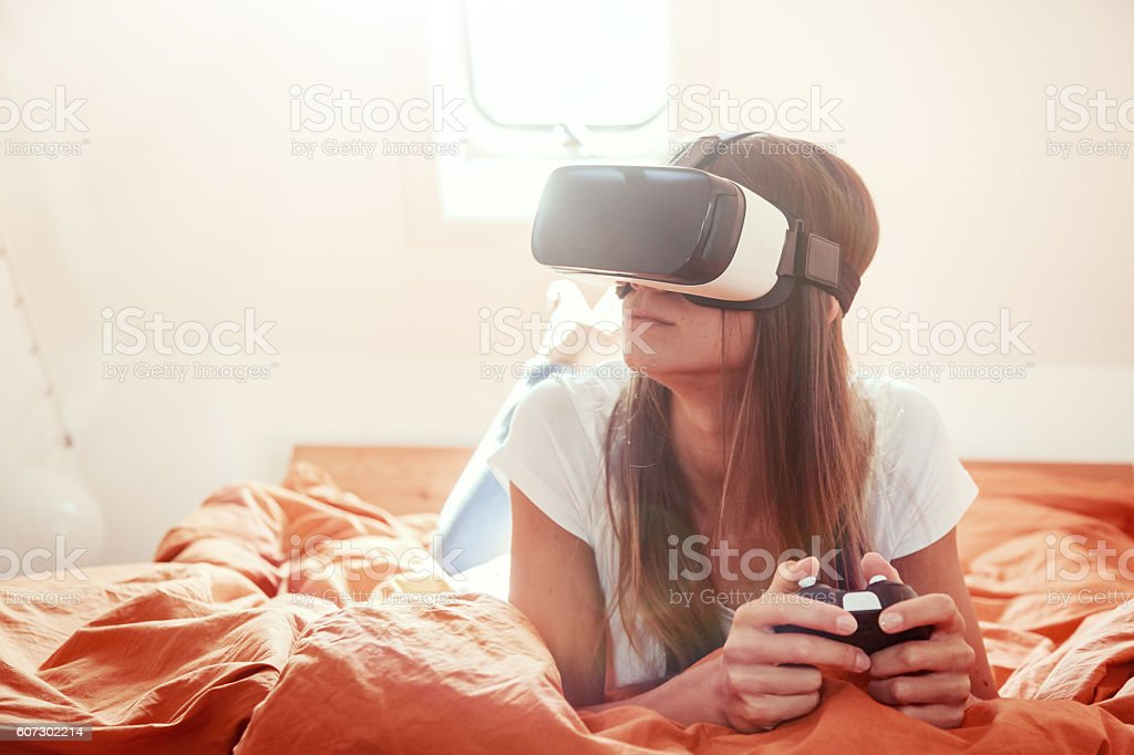 Young woman lying on bed, using VR glasses stock photo