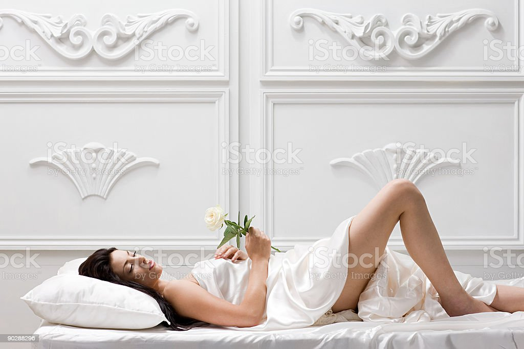 Young woman lying on bed with rose royalty-free stock photo