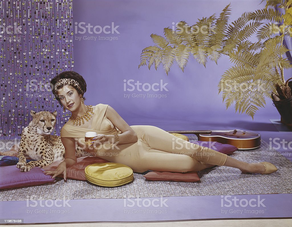 Young woman lying on cushion with leopard stock photo
