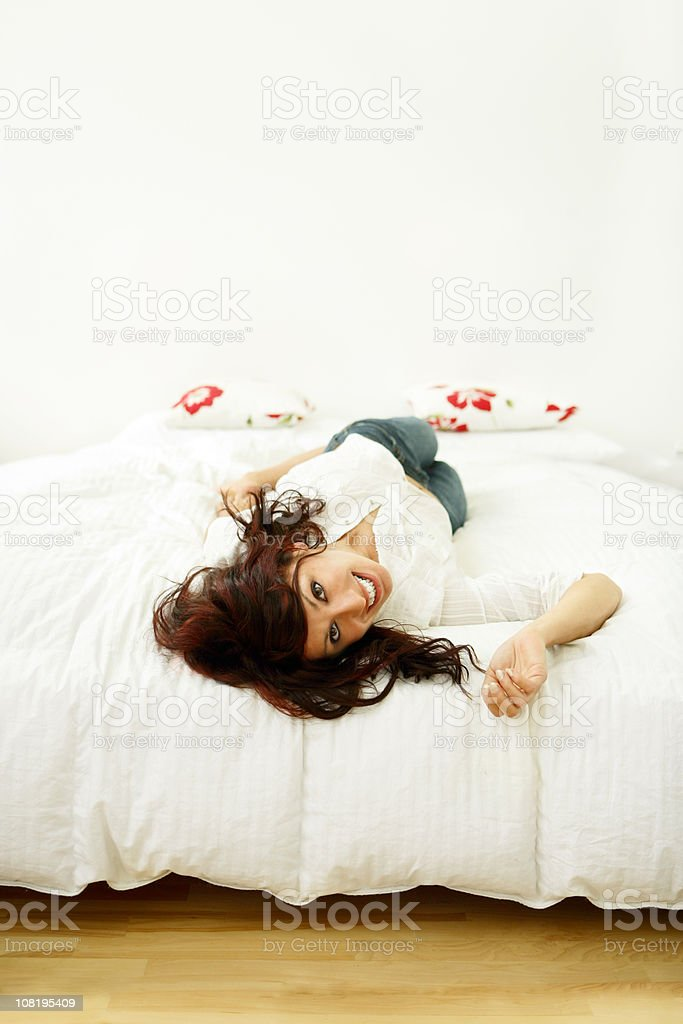 Young Woman Lying on End of Bed royalty-free stock photo