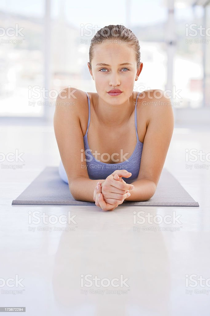 Young woman lying on exercise mat stock photo