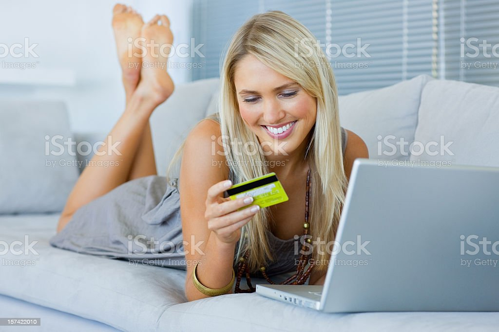 Young woman lying on front looking at credit card royalty-free stock photo