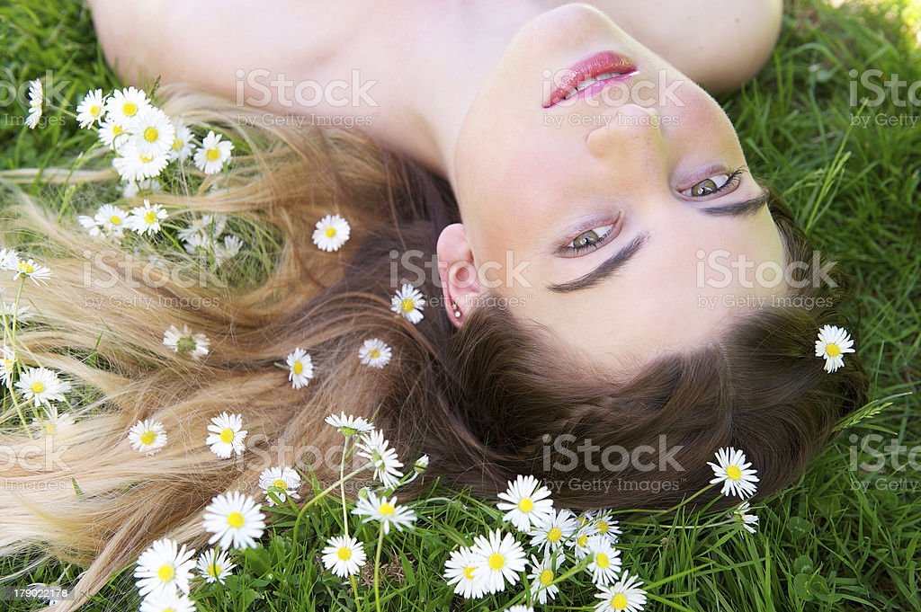 Young woman lying on grass and flowers outdoors royalty-free stock photo
