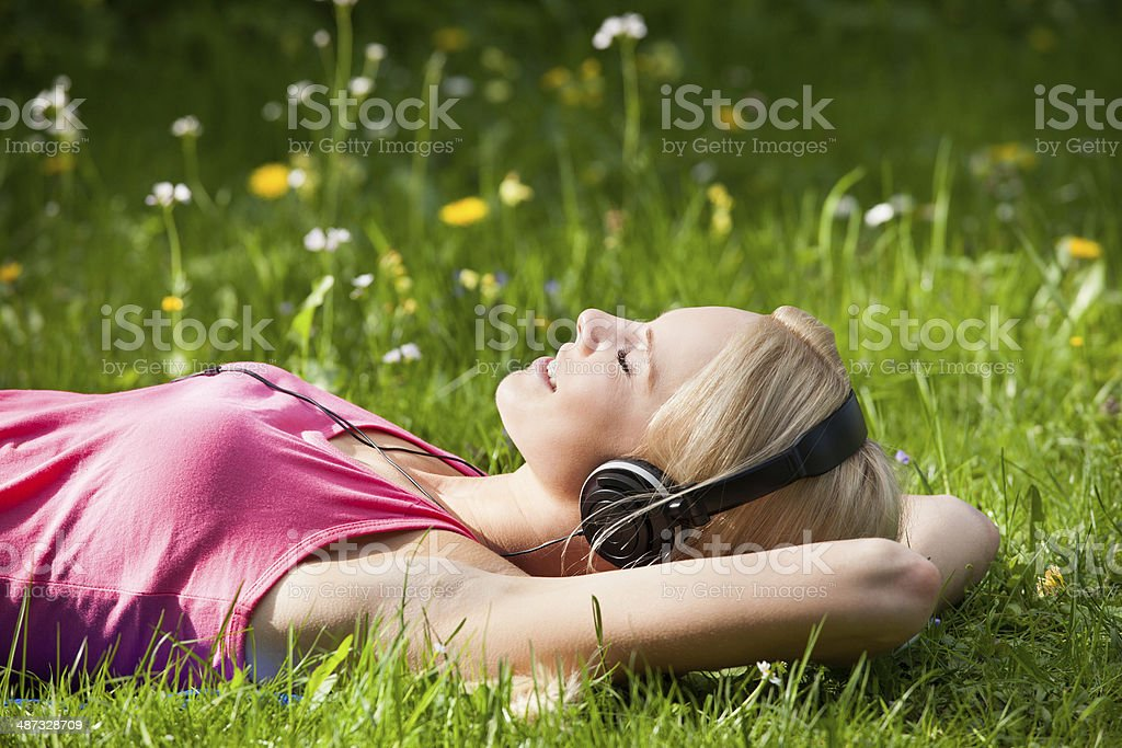 Young Woman Lying On Grass And Listening To Music stock photo