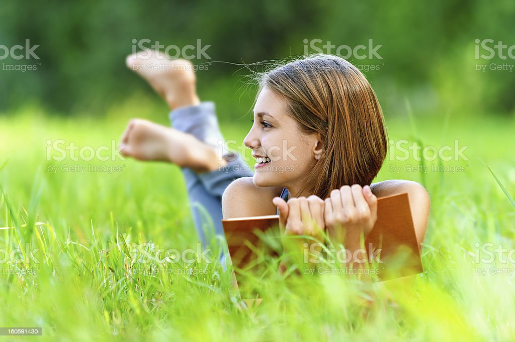 young woman lying on grass and reading book royalty-free stock photo
