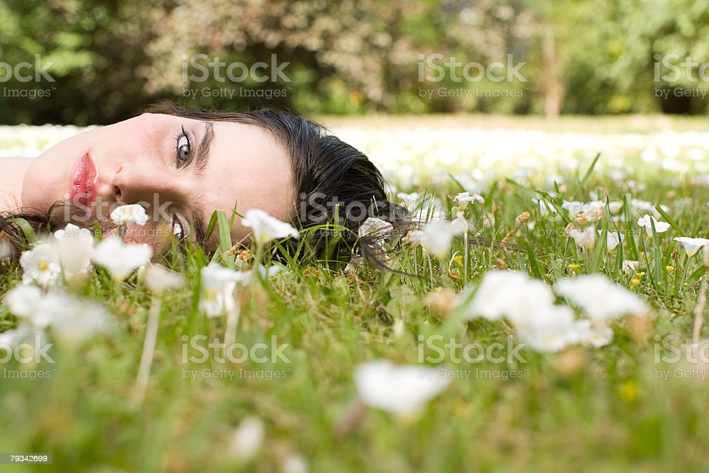 Young woman lying on grass stock photo