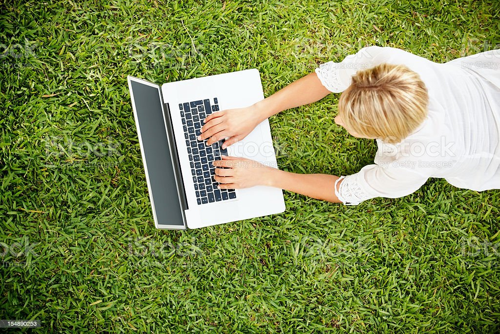 Young woman lying on green grass and using laptop royalty-free stock photo