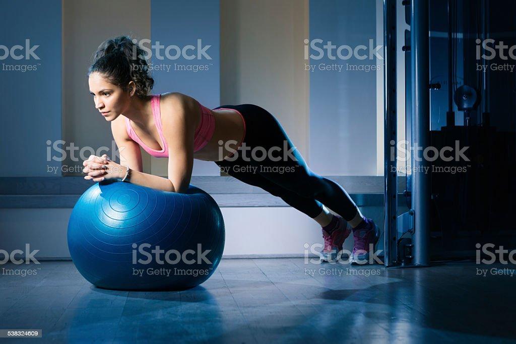 Young woman lying on gymnastic ball stock photo