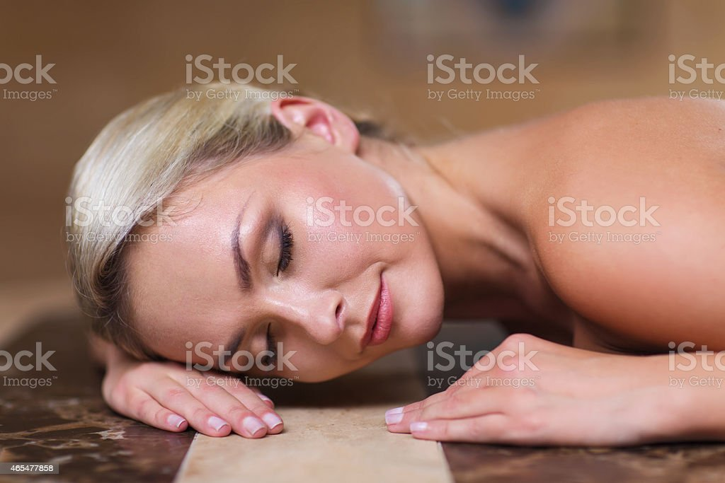 young woman lying on hammam table in turkish bath stock photo