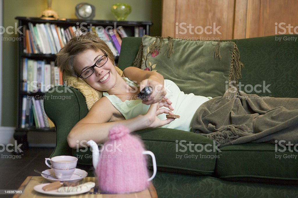 Young woman lying on her couch watching television stock photo
