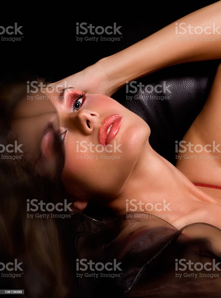 Young Woman Lying on Leather Sofa stock photo