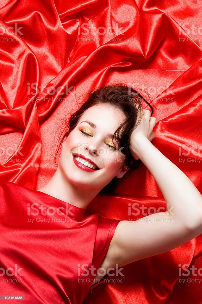 Young Woman Lying on Red Sheets stock photo