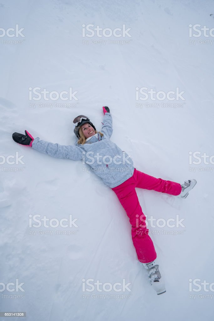 Young woman lying on snow playing snow angel stock photo