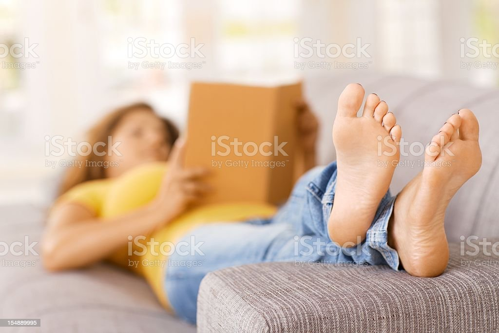 Young woman lying on sofa at home, reading stock photo