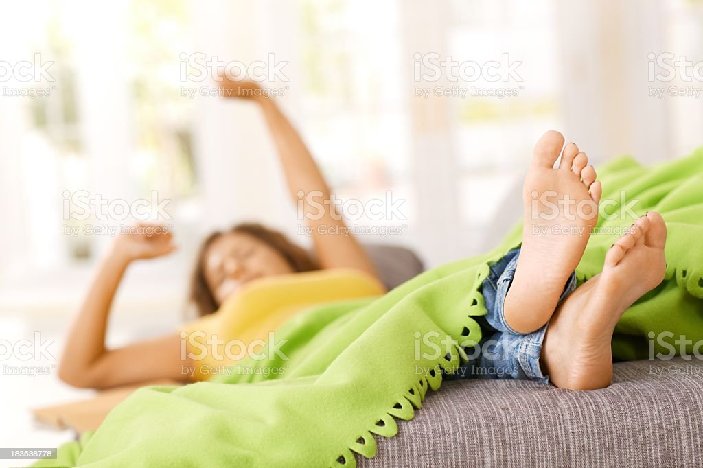 Young woman lying on sofa in living room, resting. royalty-free stock photo