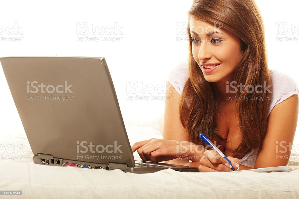 young woman lying on sofa using laptop royalty-free stock photo