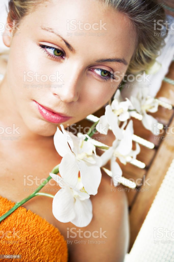 Young Woman Lying on Spa Table with Flowers royalty-free stock photo