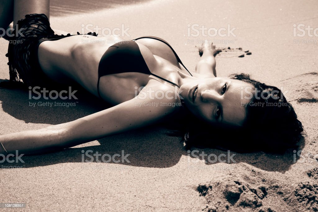 Young Woman Lying on the Beach, Sepia Toned royalty-free stock photo