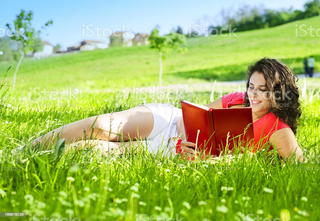 Young Woman lying on the grass and reading royalty-free stock photo