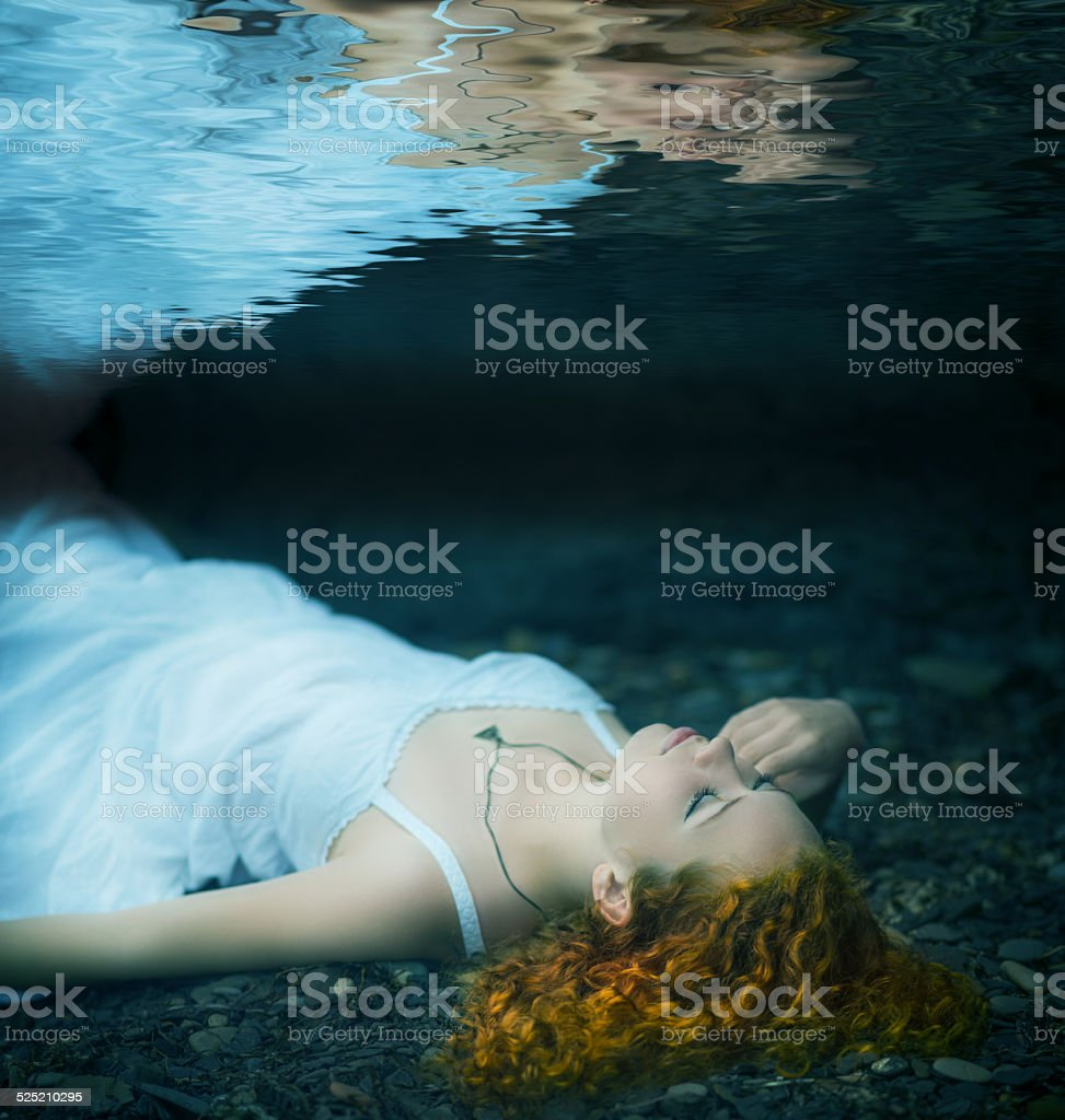 Young woman lying underwater. stock photo