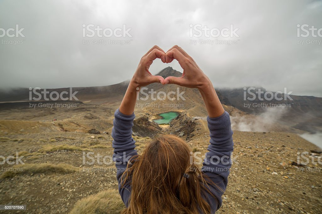 Young woman makes heart shape finger frame in nature stock photo